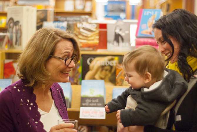 Photo of Kristin Ohlson chatting with a family - Photo by Kristin Beadle